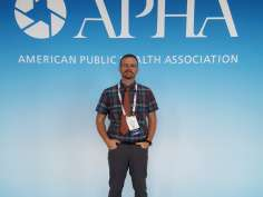 Bastyr Student standing in front of APHA blue sign